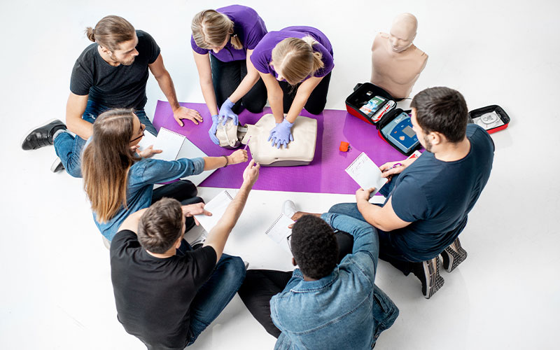 Group of people gather around a purple yoga mat to learn CPR techniques