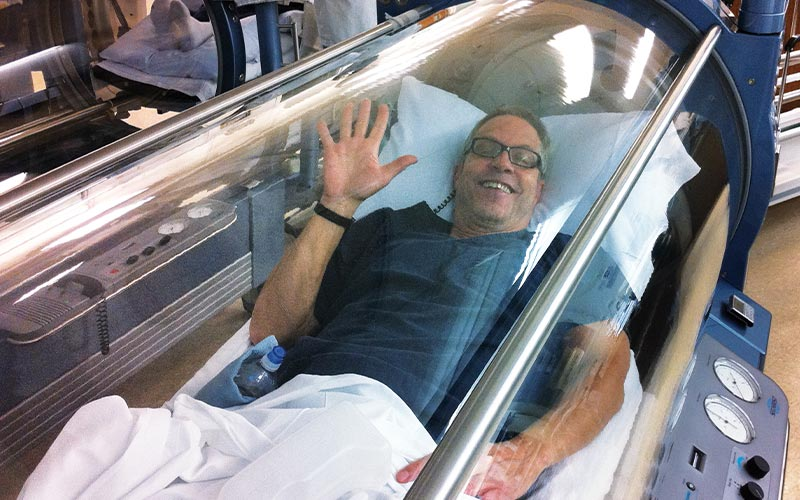 Man waves from hyperbaric chamber