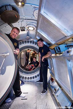 Researchers pose in two chambers and smile toward camera