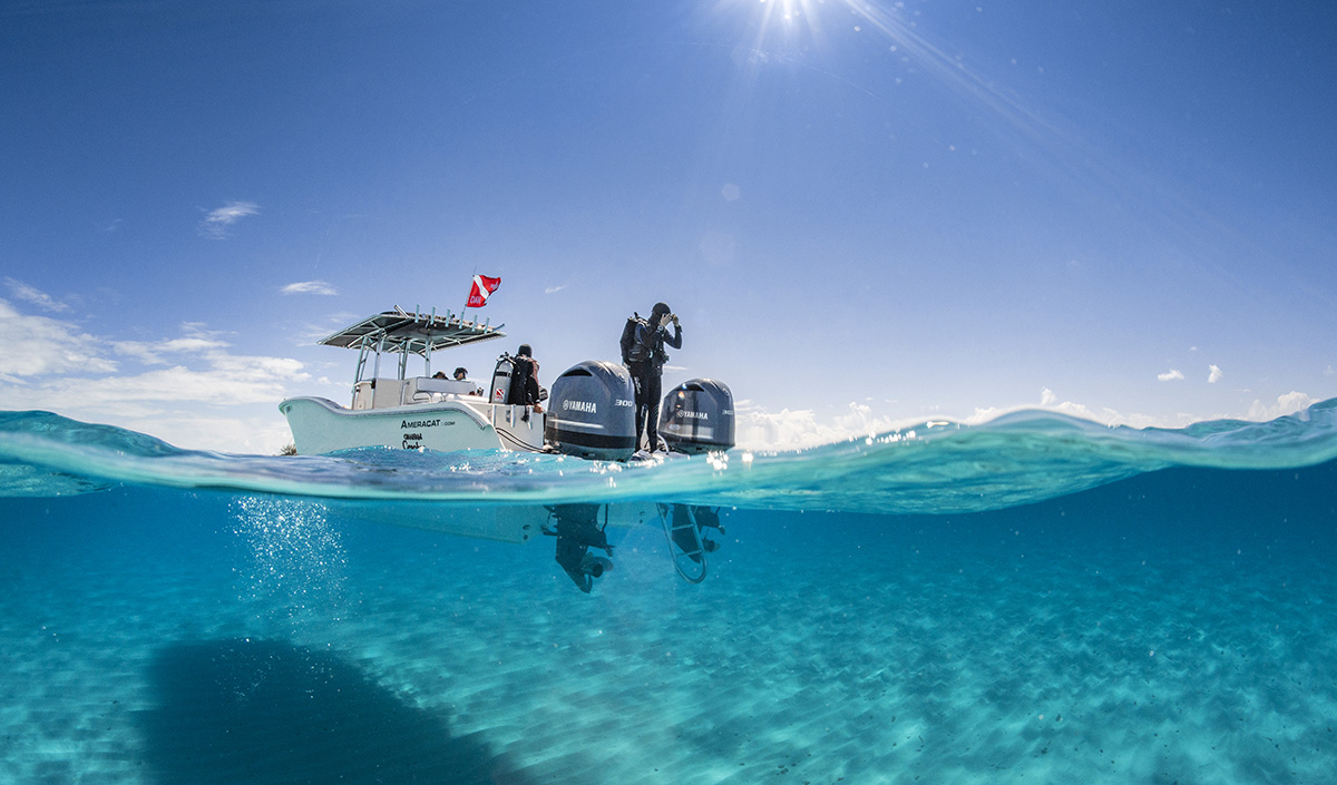 A diver is about read to jump off the boat and get into the water for a dive.