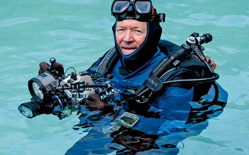 Roger Steene wears a drysuit and holds a camera, while bobbing in the water