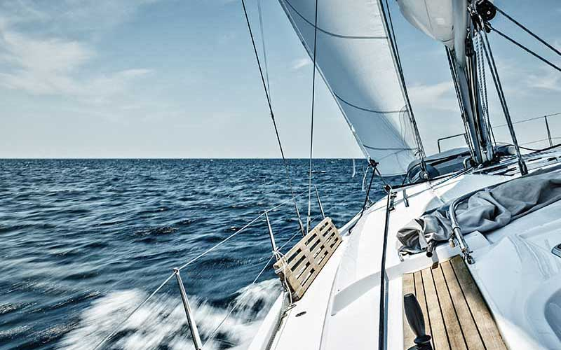 A sailboat glides down blue ocean waters