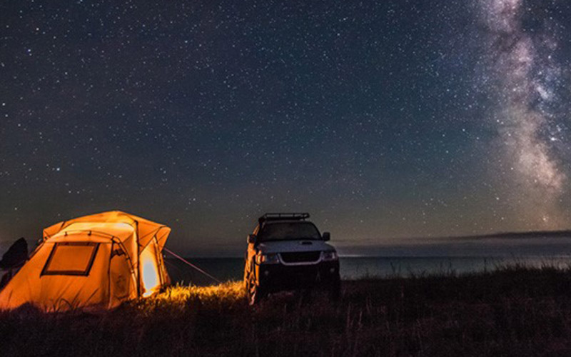 At night time, a Jeep is posed next to a lit-up tent