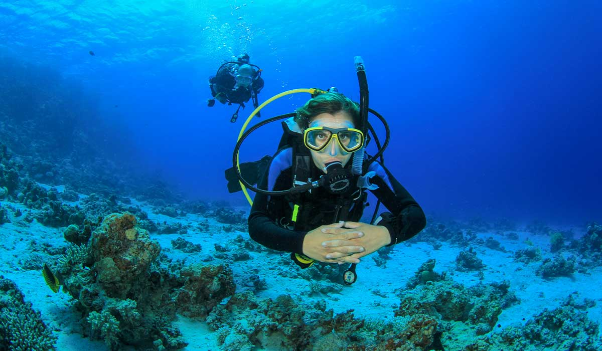 A female diver is in the foreground with her hands clasped. A male diver is in the background.
