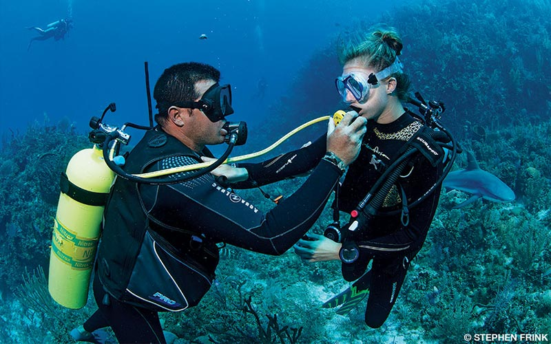 Two divers practice sharing a regulator