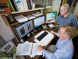 Two gentlemen discuss science around a computer