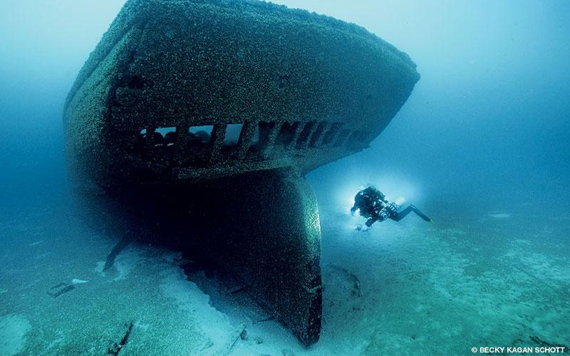 A diver explores an old wooden schooner shipwreck