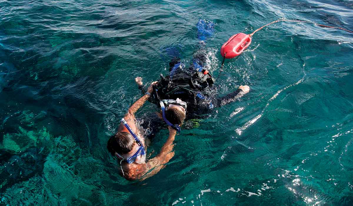 A snorkel-wearing swimmer tows another snorkeler wearer through the water