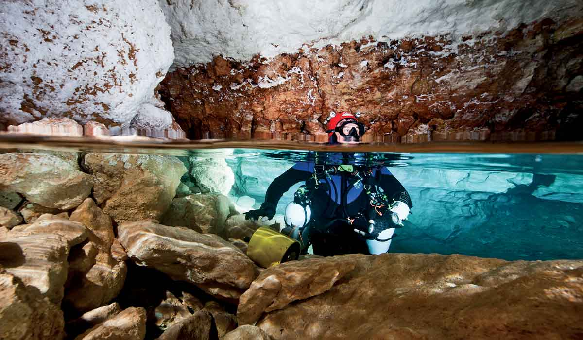 Cave diver with red hood pops head out of cavern