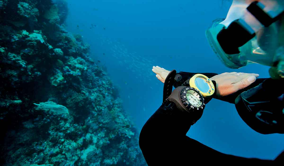 Diver charts path forward through use of a compass watch on his arm
