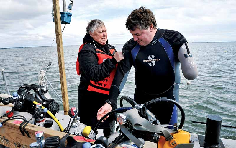 Female diver helps a male diver get suited up