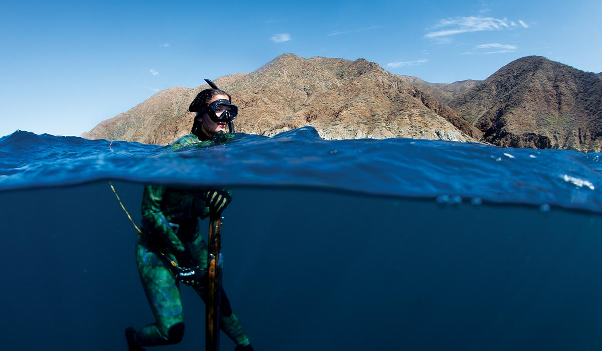 Female freediver takes a break while floating and holding her speargun