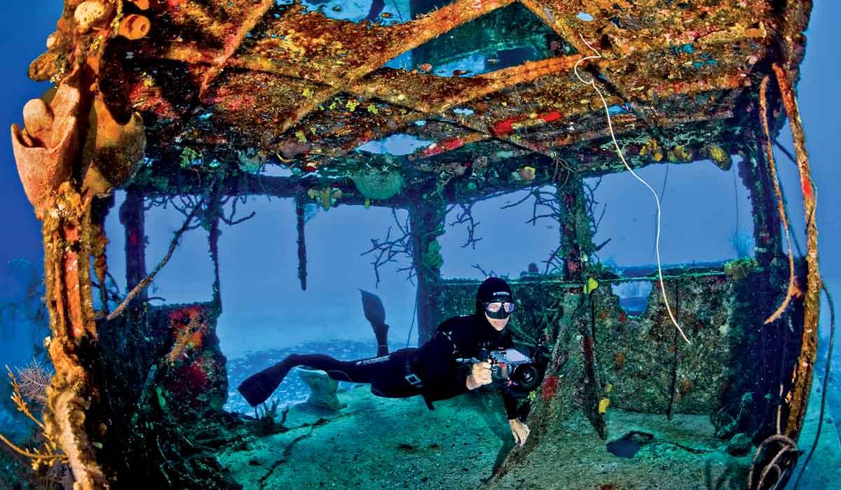 Freediver, holding a camera, swims through a wreck