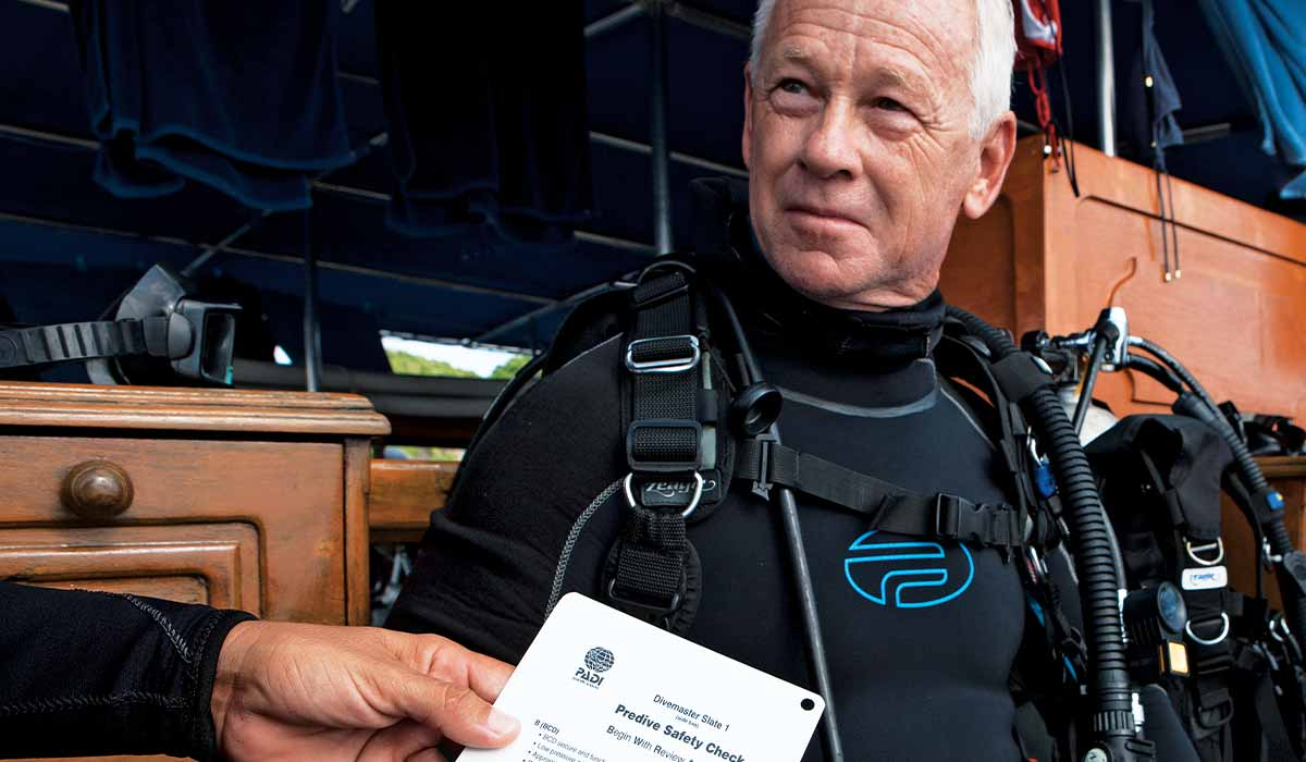 Male diver is sitting down and hand with checklist is in foreground