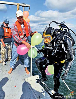 Male diver steps onto boat after a dive. Someone is holding balloons.