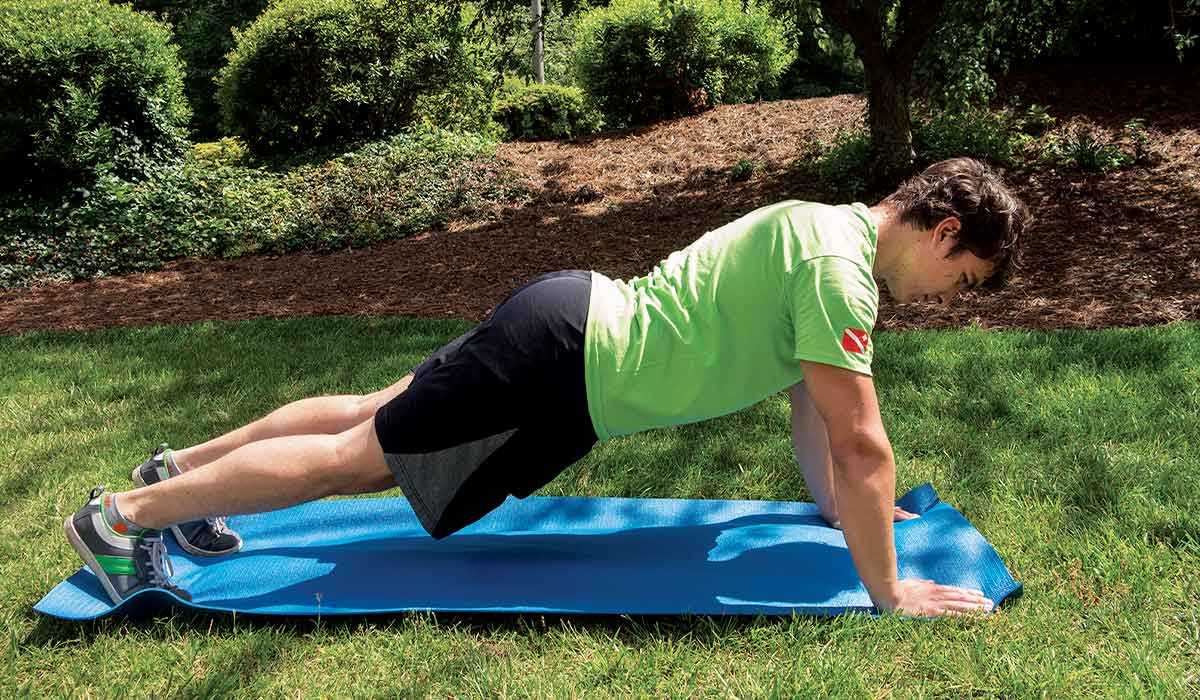 Man in green shirt holds a plank position