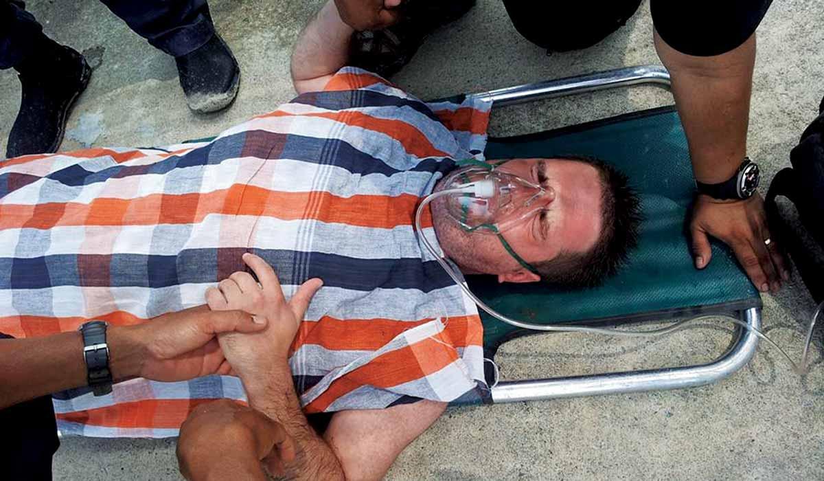 Man lies on stretcher wearing an oxygen mask