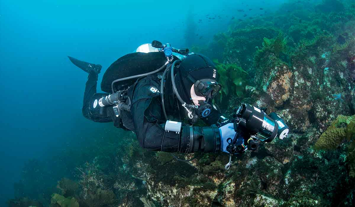 Perfectly horizontal diver approaches a reef while holding a camera