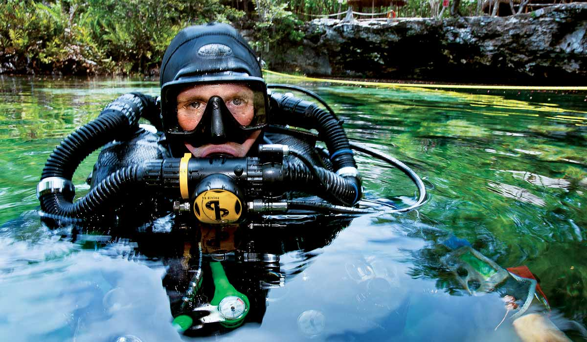 Rebreather diver pops his head out of the water