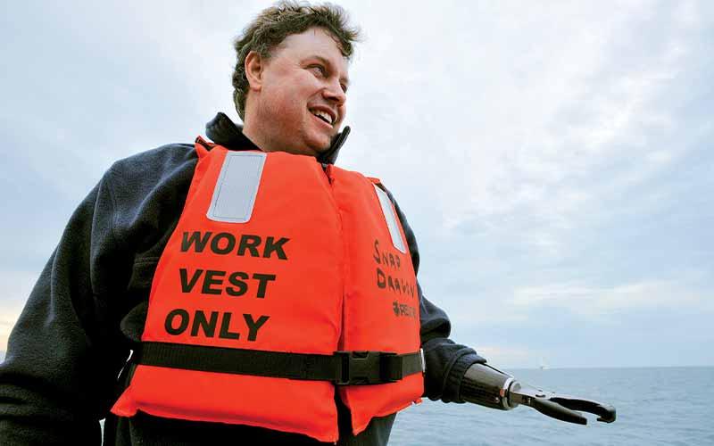 Rick Allen wears a bright orange life vest