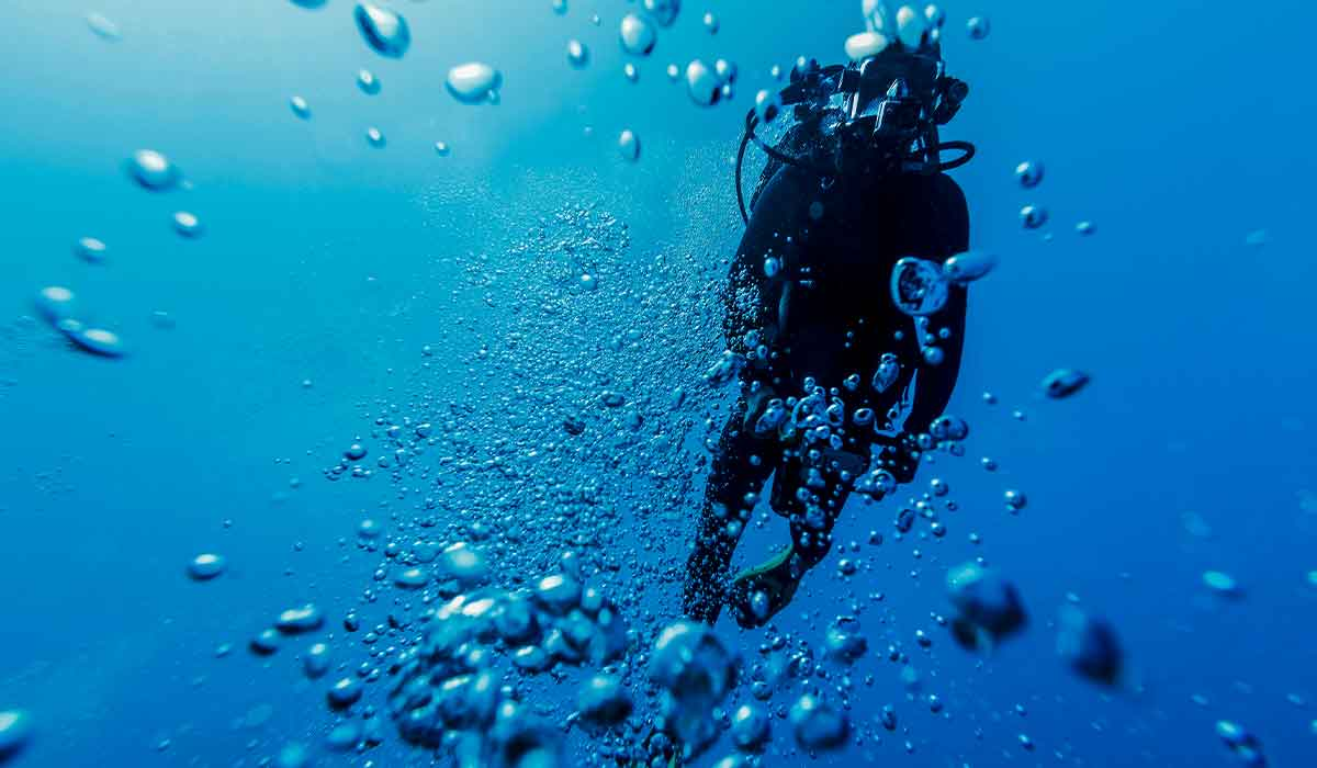 Scuba diver floats upward and is surrounded by bubbles