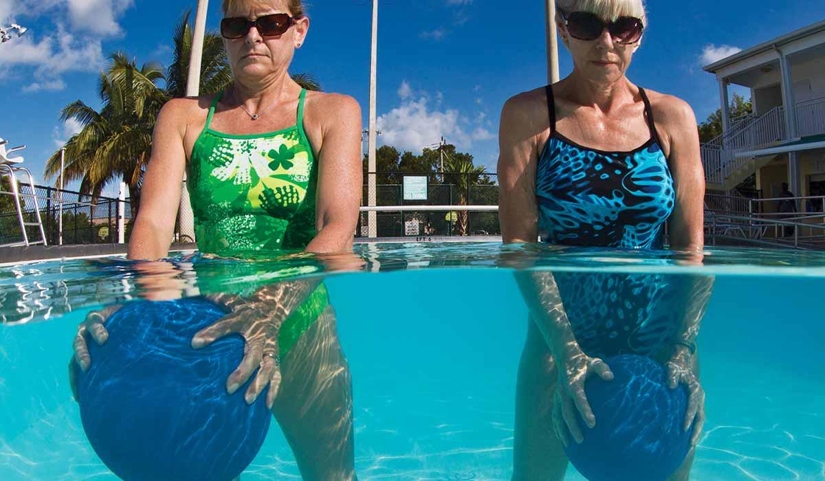 Split shot of two women in a pool each holding blue balls