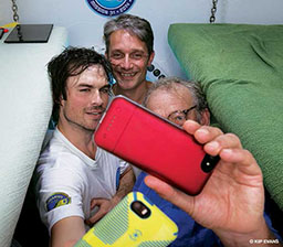 Three men cram together in a tight space to take a selfie