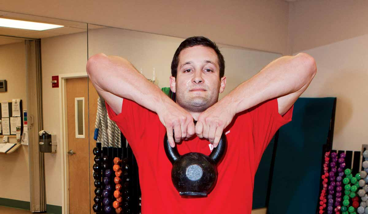 Torso of man in red short holding a kettlebell up to his chin