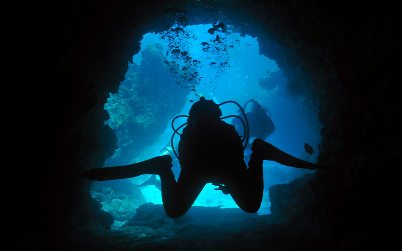 Two divers swim through a cave