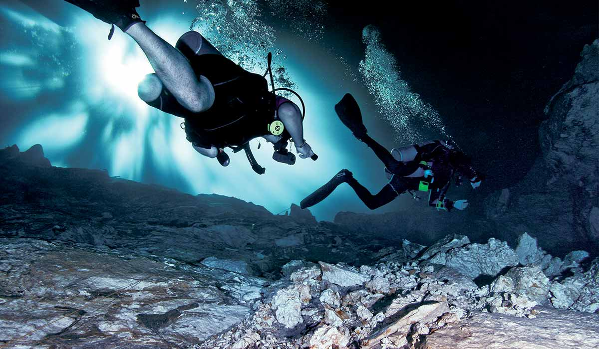 Two divers swim over jagged rocks