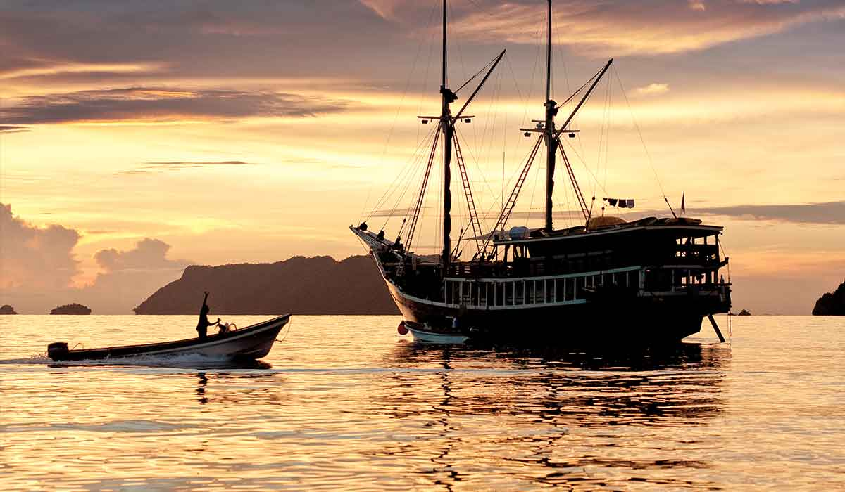 A liveaboard boat, that looks like a pirate ship, at sunset