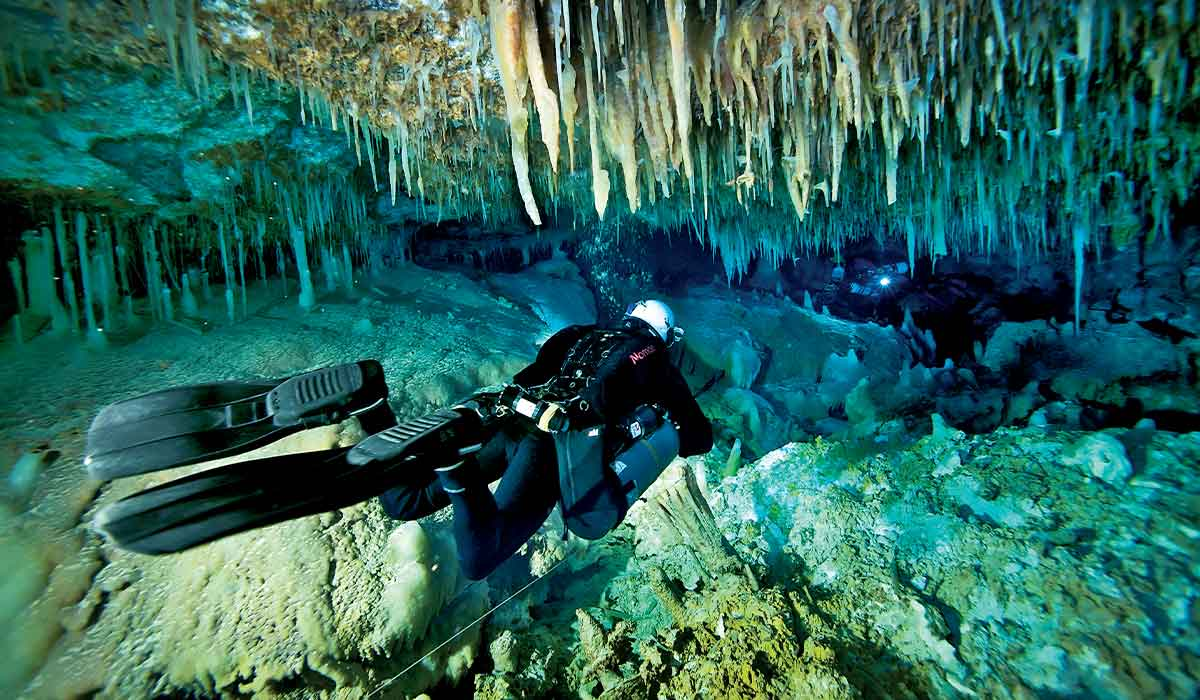 Cave diver with side-mounted tanks swims through a narrow passage