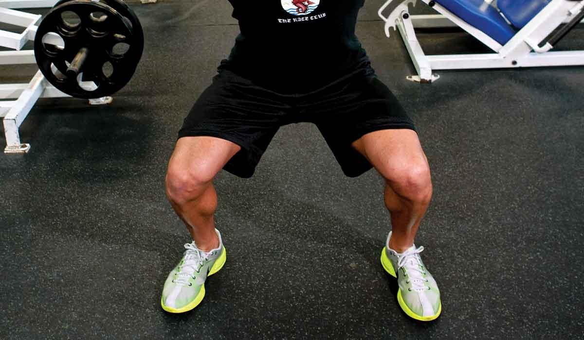 Close-up photo of a man performing a squat