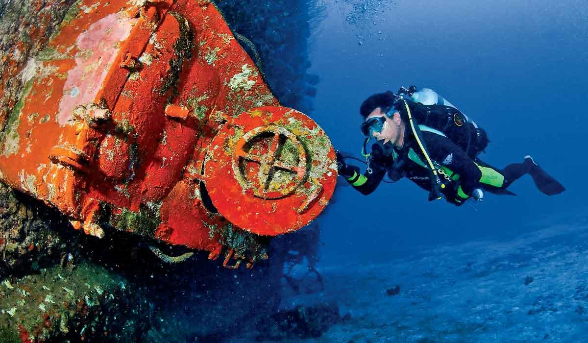 Diver opens the door of a shipwreck