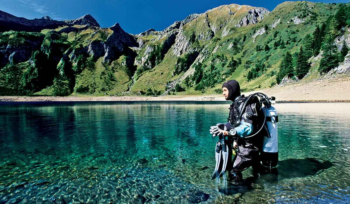 Diver walks into mountain lake to start dive