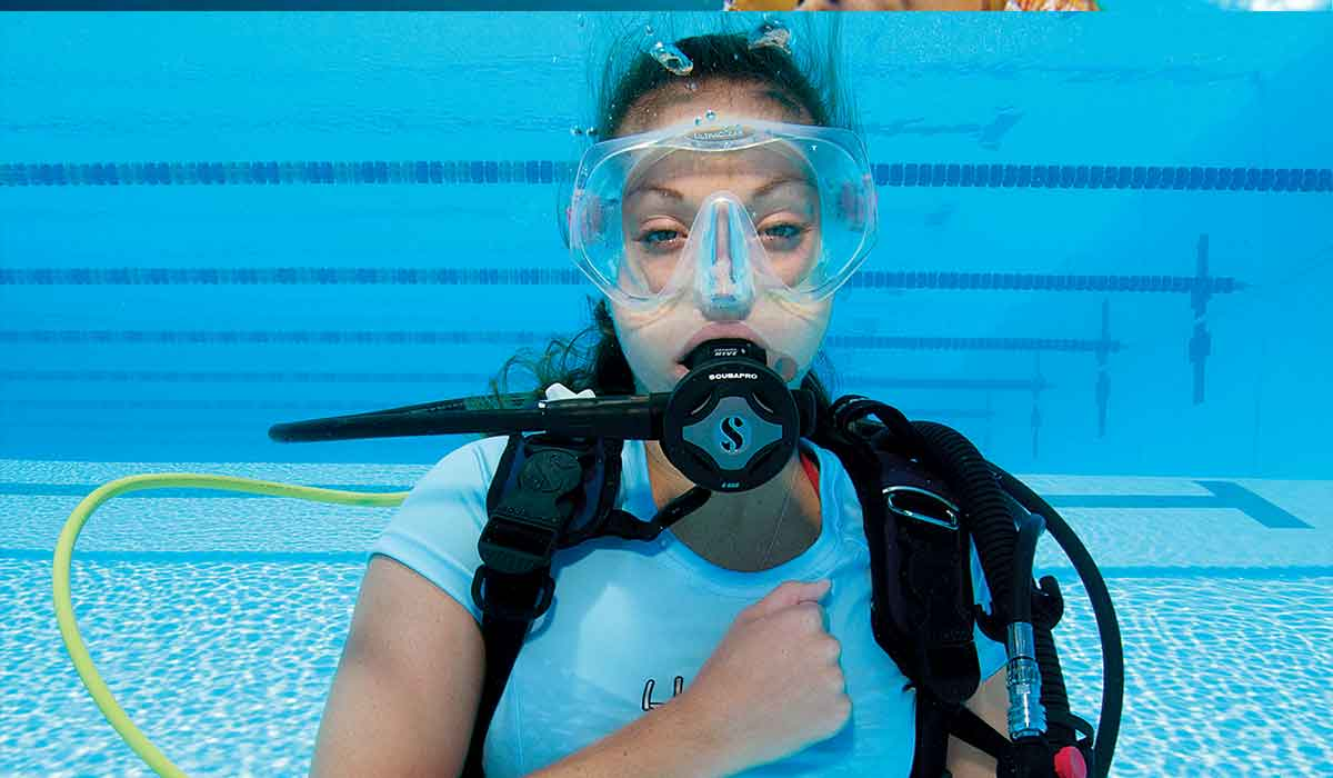 Female diver holds right fist to chest