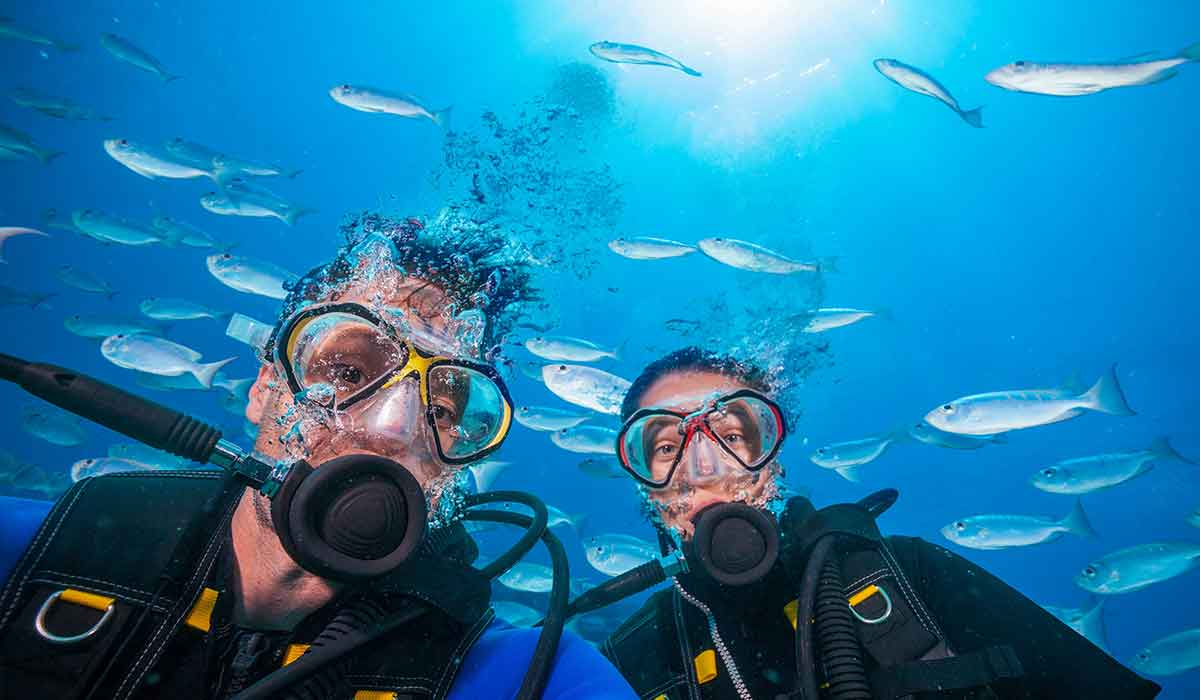 Male and female diver pose for a selfie in front of school of silver fish
