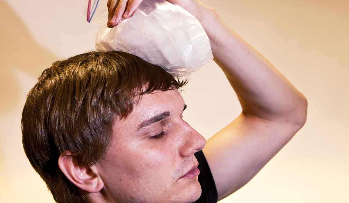 Man holds ice pack to his bonked head