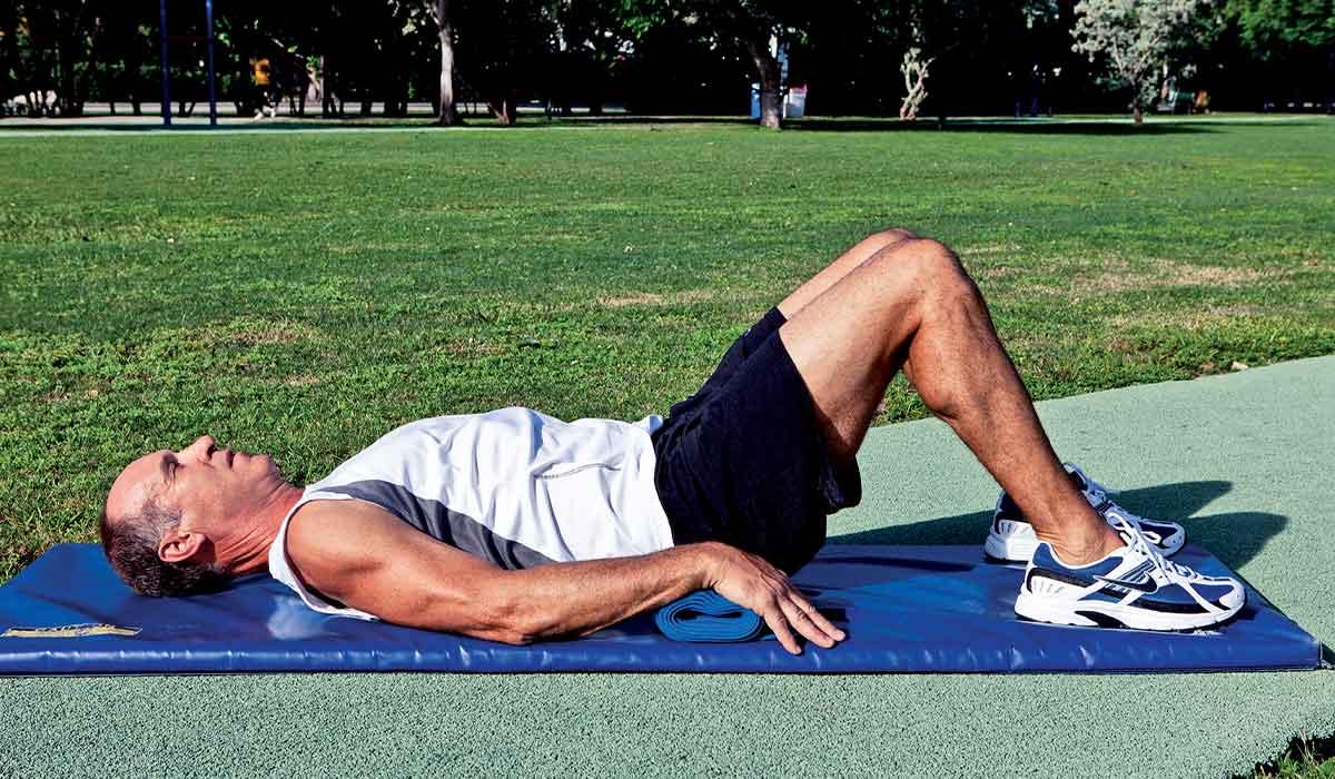 Man lies on blue mat with knees bent
