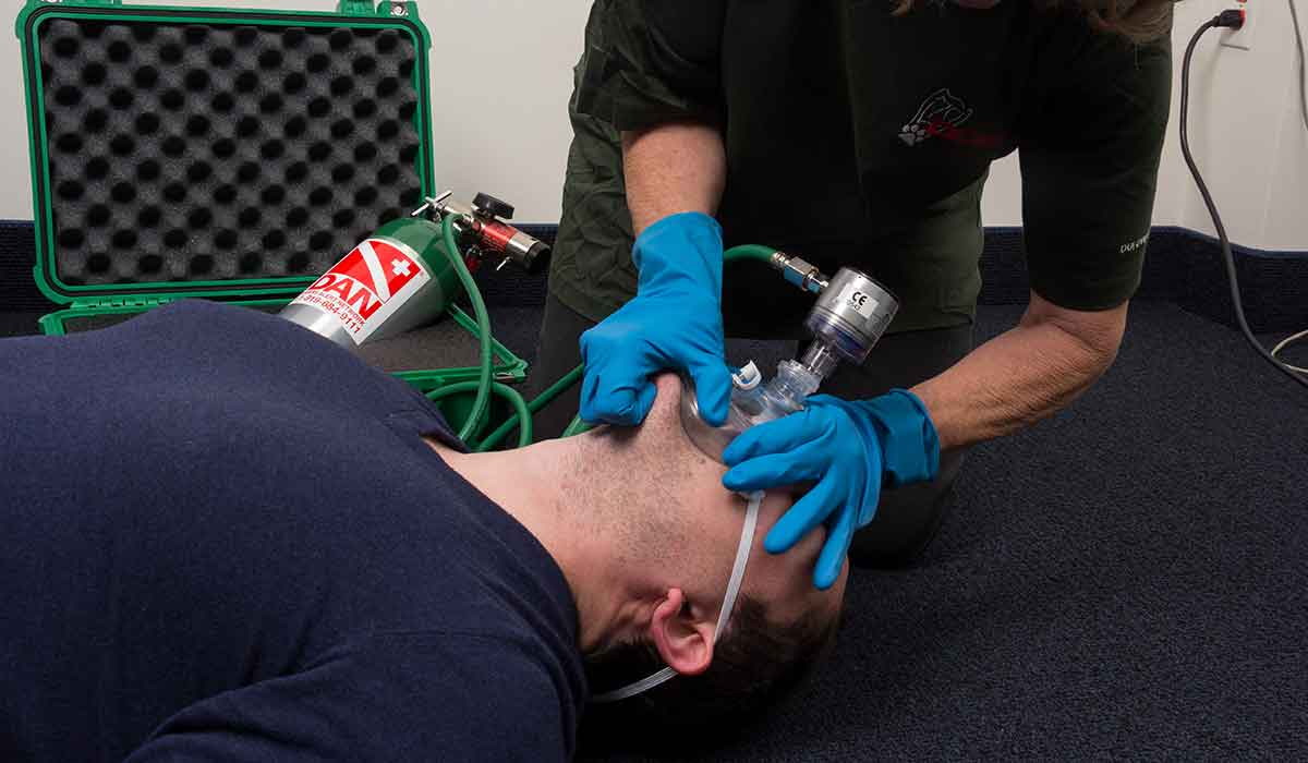 Man receives emergency oxygen while lying on carpet