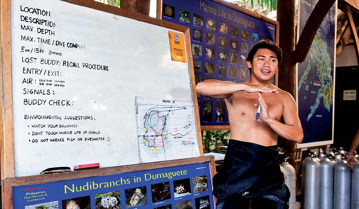 Shirtless dive master leads a predive check with white board