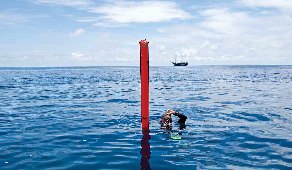 Surfaced diver floats next to red marker