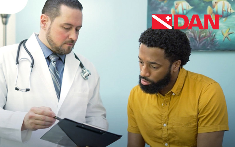A Black patient in a yellow shirt gets advice from a bearded doctor