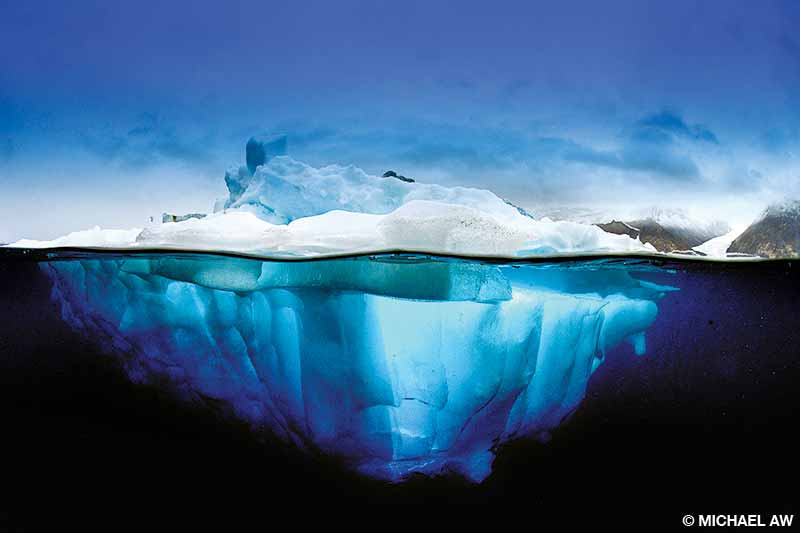 An over-under photo of an iceberg with the fast-eroding mountain glacier in the background at Scoresby Sund, Greenland