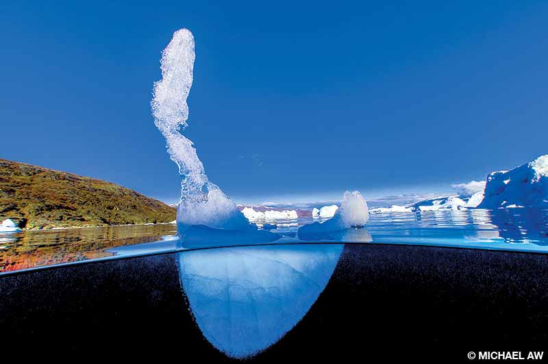 The remains of a once-mighty iceberg beneath a warm blue sky at Scoresby Sund, Greenland