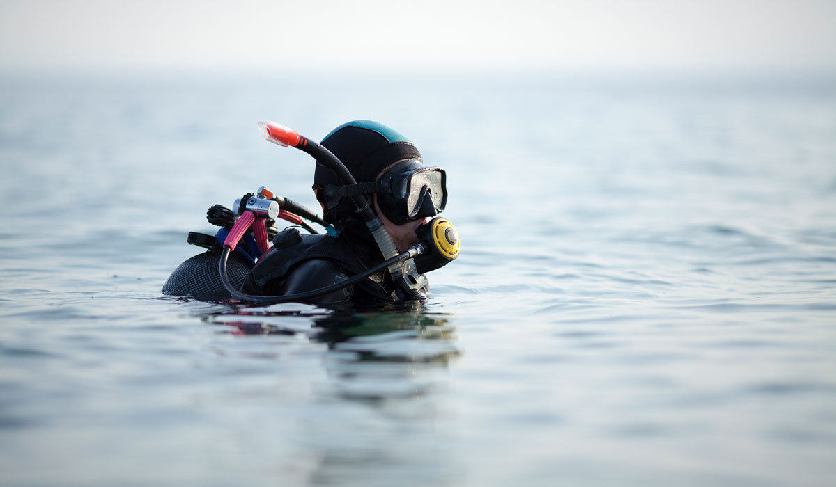 With a regulator still in their mouth, a drysuit diver pauses at the surface of the water